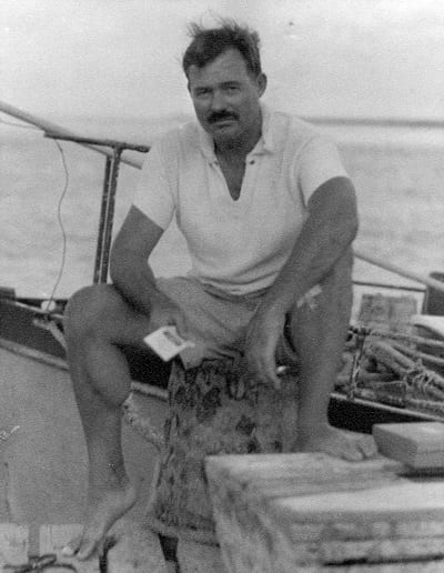 Ernest Hemingway sitting on a dock next to the Pilar,