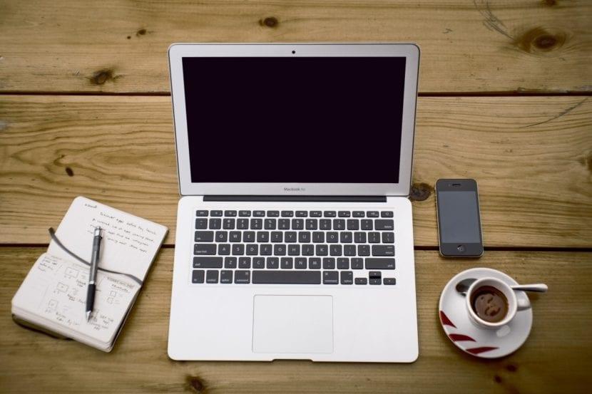 Ordenador, libreta y café