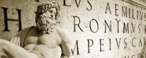 Escultura en frente de una pared con grabados en latín.